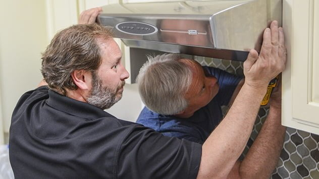 Danny Lipford and homeowner Kenneth Sigler install the range hood.