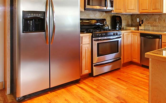 Kitchen with wood floor and a focus on the refrigerator coils