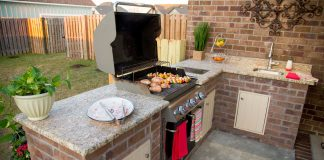 Outdoor kitchen with brick grill surround and wood doors, as seen on Today's Homeowner.