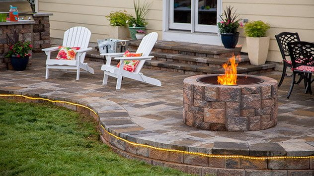 One end of the patio features a paver retaining wall and a fire pit.