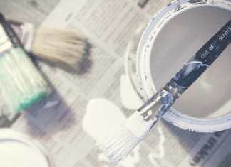 Paint with no volatile organic compounds opened. The paintbrush is on top of the can.