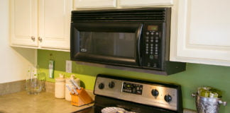 An over-the-range microwave oven in kitchen with green walls and laminate countertops