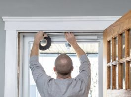Man replaces weatherstripping in door frame
