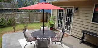 Concrete patio with dining set and umbrella