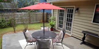 Concrete patio with dining set and umbrella