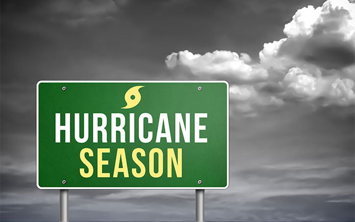 Interstate sign that says, hurricane season, against a black-and-white cloudy background.