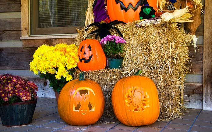 Front porch fall display featuring jack-o-lanterns and bales of hay