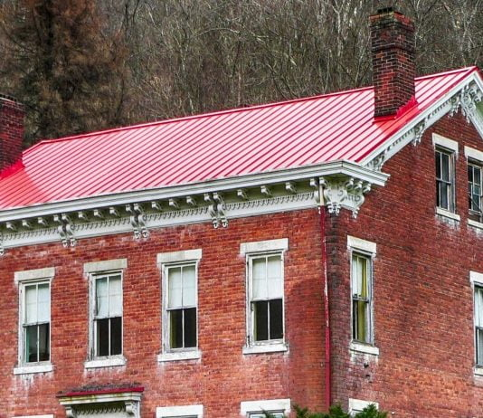 Red metal roof on brick home, as seen on an overcast day