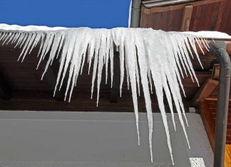 Icicles hanging from the edge of a residential roof