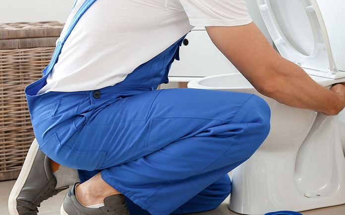 Man in overalls squats as he installs a white porcelain toilet