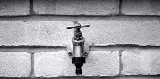 Outdoor faucet, seen close up, in grayscale.