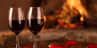 Wine glasses and rose petals, set on a table, in front of a roaring fire, on Valentine's Day