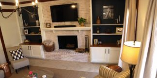 Lightened den featuring a flat-screen TV, fireplace and bookcase
