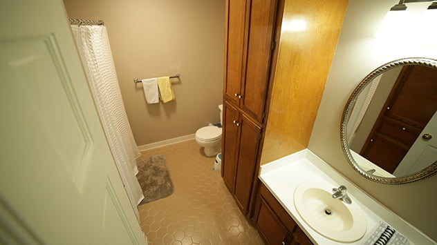 A dark, unattractive bathroom with dated cabinets and features, before the renovation