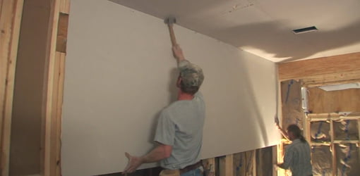 Hanging drywall on walls of bedroom addition.