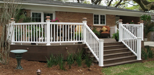 Completed composite deck and railings in backyard of home.