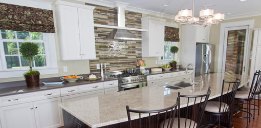 Remodeled kitchen with granite countertops and range hood.