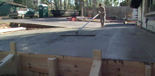 Smoothing the recently poured concrete slab for the addition.