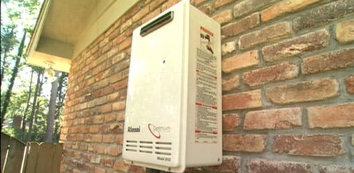Tankless hot water heater mounted outside on a brick wall.