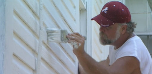 Painting siding on a house.