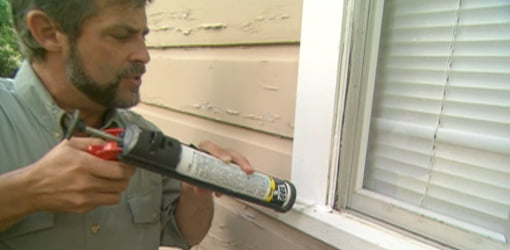 Applying caulk to a window.