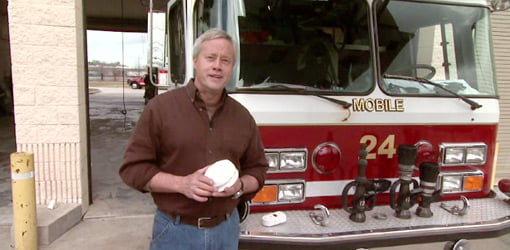 Danny Lipford with smoke detector in front of fire truck.