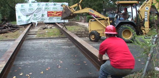I-beams are positioned under Aaron home for moving.