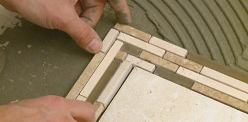 Alabaster porcelain tile with a mosaic pattern ribbon tile inlay