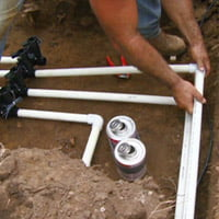 PVC pipes for lawn irrigation routed into manifold