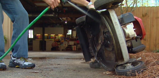 Cleaning under a lawn mower with garden hose