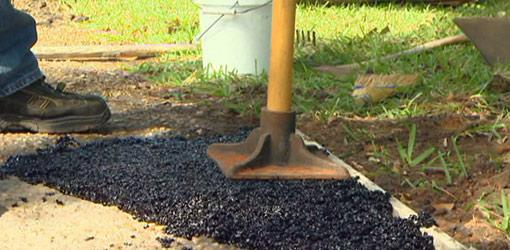 Tamping down asphalt repair material in a driveway