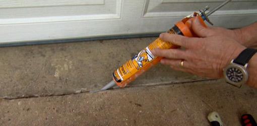 Filling a crack in a concrete driveway with concrete repair caulk