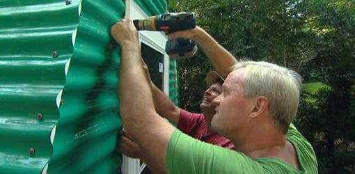 Attaching storm door to greenhouse with screws.