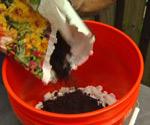 Pouring potting soil on foam peanuts in 5 gallon bucket