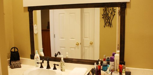 Custom made stained wood frame added to bathroom mirror
