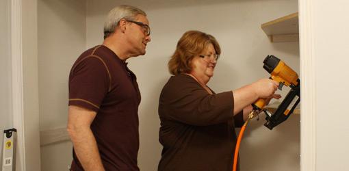 Danny Lipford assisting homeowner use nail gun in closet makeover.