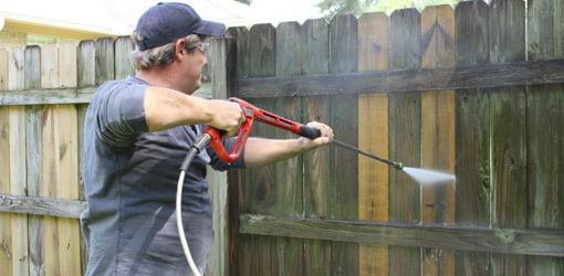 Cleaning a fence with a pressure washer