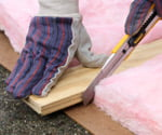 Cutting fiberglass insulation with long utility knife.