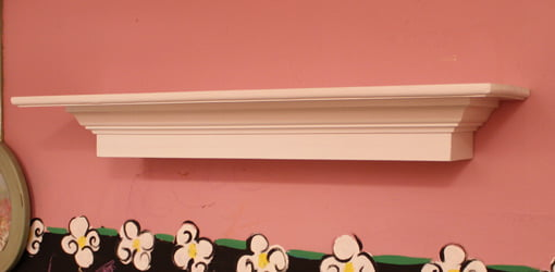Floating decorative wall shelf mounted on pink wall in child's room.