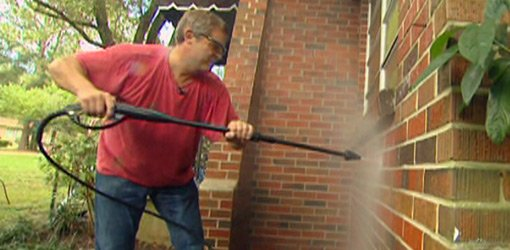 Cleaning brick with pressure washer.