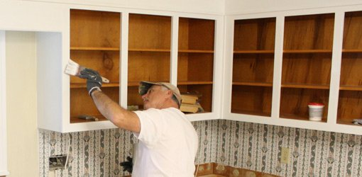 Painting the existing kitchen cabinets with oil-based paint.