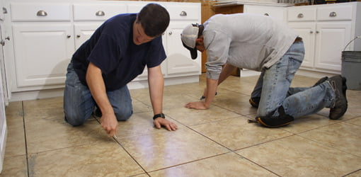 Laying the ceramic tile kitchen floor.