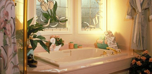 Soaking bathtub with stained glass window.