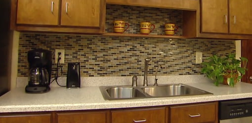 Completed kitchen with mosaic tile backsplash, decorative shelf, and water filter.