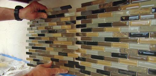 Setting mosaic tile backsplash in thin-set adhesive.