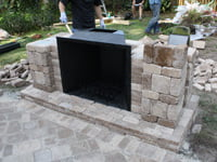 Constructing outdoor paver fireplace.