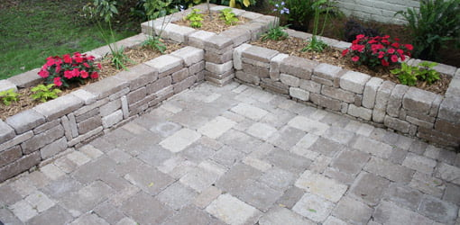 Completed paver patio with planter beds.