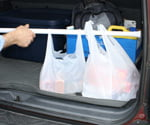 Grocery bags secured in back of car with shower curtain rod.