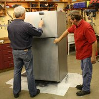 Applying stainless steel coating to a refrigerator.