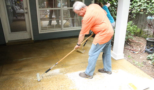 Applying concrete stain to patio.